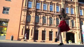 A girl in a red skirt and a black topic shows the movement from the street dance while she is being photographed, slow stock video footage