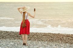 Girl in red skirt and hat making selfie on the beach on sea and sky background. View from the back.  Stock Images