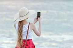 Girl in red skirt and hat making selfie on the beach on sea and sky background. View from the back.  Royalty Free Stock Photos