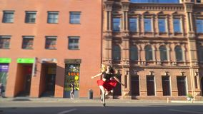 A girl in a red skirt laughs and makes a twine in a jump, slow motion stock video