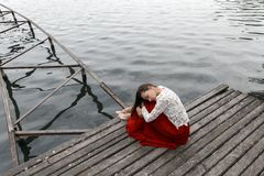 Lonely european girl in red skirt on the bridge. A girl in a red skirt sits on a bridge near the sea Royalty Free Stock Photography