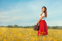 Girl in a red skirt with suitcase. Royalty Free Stock Images