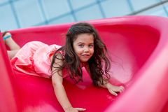 Girl on red slide Royalty Free Stock Photos
