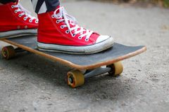 Girl in red sneakers on a skateboard. Feet on a skateboard stock images