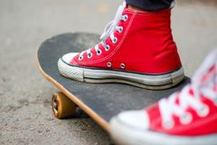 Girl in red sneakers on a skateboard. Feet on a skateboard royalty free stock photo