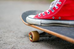 Girl in red sneakers on a skateboard. Feet on a skateboard stock image