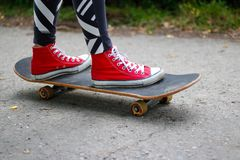 Girl in red sneakers on a skateboard. Feet on a skateboard stock photo