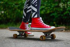 Girl in red sneakers on a skateboard. Feet on a skateboard stock photography