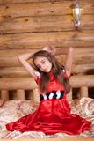 Girl in red spanish dress sitting on bed Royalty Free Stock Photography
