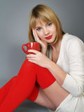 Girl in red stockings with a mug Stock Photos