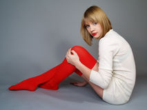 Girl  in red stockings sits on a floor Stock Photos