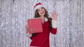 Girl in a snow maiden costume holds a gift in her hand and waves her hand, hello. Bokeh background. Slow motion stock footage