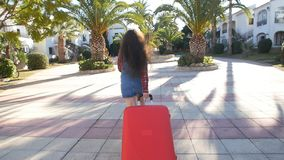 Toung woman with a red suitcase running on a resort. Girl with a red suitcase on a resort stock footage