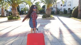 Toung woman with a red suitcase running on a resort. Girl with a red suitcase on a resort stock video footage