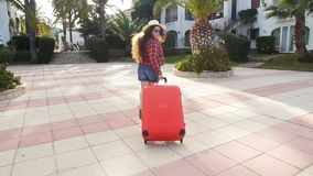 Toung woman with a red suitcase running on a resort. Girl with a red suitcase on a resort stock video
