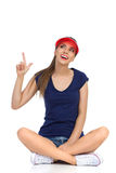 Girl In Red Summer Visor Cap Pointing Up. Smiling young woman in blue shirt, and red sun visor cap sitting on a floor with legs crossed, looking up and pointing Stock Photos