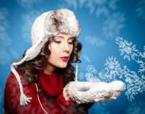 Girl in a red sweater blows away the snowflakes on his hands Stock Photo
