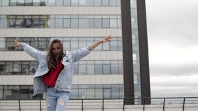 Dancing girls on the roof. A girl in a red sweater is dancing on the town roof stock video