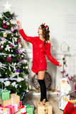 Girl in a red sweater is decorated Christmas tree. New Year conc Stock Photo