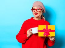 Girl in red sweater with gift box and cup of coffee royalty free stock image