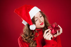 Girl in red sweater holding Christmas present wearing Santa Clau Royalty Free Stock Images