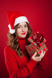 Girl in red sweater holding Christmas present wearing Santa Clau Stock Photos
