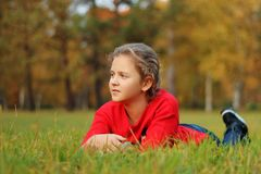 The girl lies on the green grass in the park Stock Photography