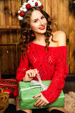 Girl in a red sweater opening Christmas gift. New Year concept Royalty Free Stock Photography