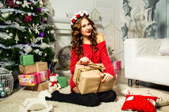 Girl in a red sweater opening gift near the Christmas tree. Chri Royalty Free Stock Images