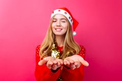 Girl in red sweater, Santa hat and tinsel on neck, holding something invisible on palms isolated on red background. The concept of a Christmas gift stock photography