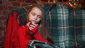 Girl in a red sweater thoughtfully sits with a cup of tea stock video