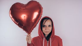 A girl in a red sweatshirt in her hand a red balloon in the form of a heart. Student posing on white background royalty free stock image