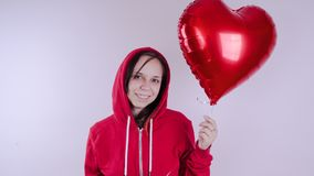 A girl in a red sweatshirt in her hand a red balloon in the form of a heart. Student posing on white background stock image