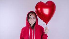 A girl in a red sweatshirt in her hand a red balloon in the form of a heart. Student posing on white background stock photo