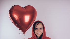 A girl in a red sweatshirt in her hand a red balloon in the form of a heart. Student posing on white background royalty free stock photos