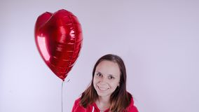 A girl in a red sweatshirt in her hand a red balloon in the form of a heart. Student posing on white background stock photography