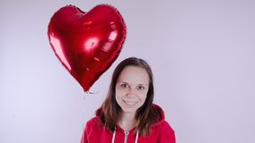 A girl in a red sweatshirt in her hand a red balloon in the form of a heart. Student posing on white background stock images
