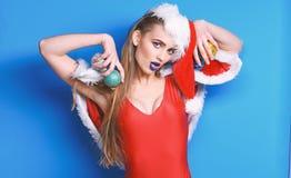 Girl Red Swimsuit And Santa Hat Hold Christmas Ball Decoration. Santa Girl Christmas Party Masquerade. Sexy Christmas Stock Photos