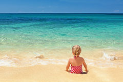 Girl in red swimsuit sitting on the sand beach edge Stock Photos