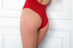 A girl in a red swimsuit is standing sideways leaning against a Royalty Free Stock Images