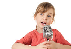 Girl in red T-shirt sing in old style microphone. Pretty little girl in red T-shirt sing in old style microphone isolated on white background, looking aside Royalty Free Stock Image