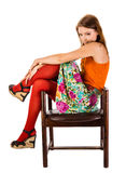 The girl in red tights sits in an old wooden chair. The girl in red tights and orange tank top sitting in an old wooden chair isolated on white Royalty Free Stock Photography