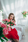 Girl with red tulips Stock Images