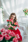 Girl with red tulips Stock Photography
