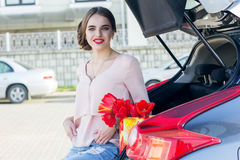 Girl with red tulips sitting in car trunk Stock Photo