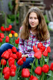 Girl in red tulips Stock Images