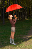 Girl with a red umbrella. The young girl with a red umbrella in autumn park Royalty Free Stock Image
