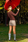 Girl with a red umbrella. The young girl with a red umbrella in autumn park Stock Image