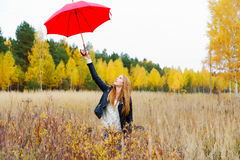 The girl with a red umbrella in autumn Stock Image