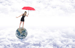 Girl with red umbrella on planet earth represented as a balloon Stock Image